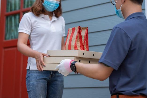 Азиатская женщина в маске получает упаковку с едой от доставщика на дом концепции карантинного пандемического вируса коронавируса [covid-19].