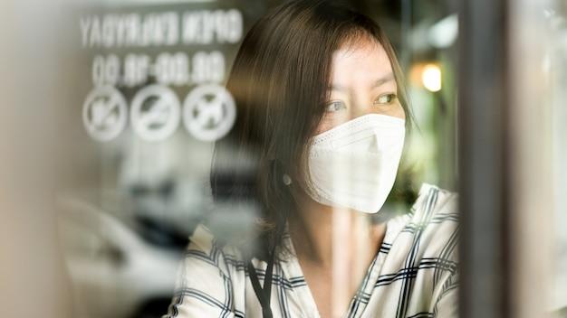 의료용 마스크를 쓴 아시아 여성이 카페에서 창 밖을 내다보며 슬픈 눈을 하고 집에서 일하고 격리합니다.