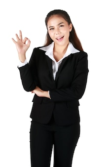 Asian woman wearing black suit against a white background isolated winks an eye and holds an okay gesture with hand. concept ok success.