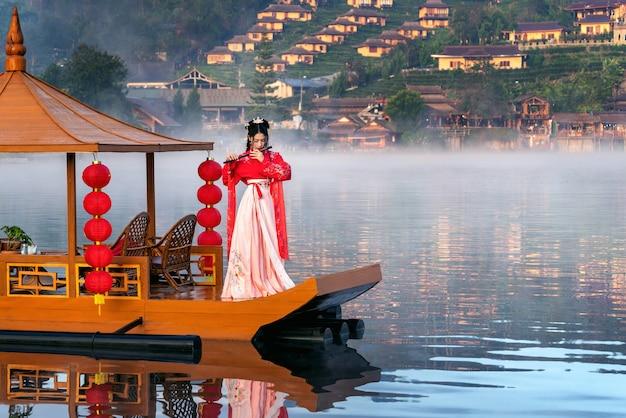 Donna asiatica che indossa abiti tradizionali cinesi sulla barca yunan al villaggio tailandese di ban rak nella provincia di mae hong son, thailandia