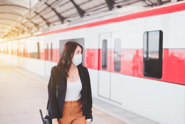 フェイスマスクを着用し、駅に立っているアジアの女性、公共交通機関の安全性、covid-19パンデミック中のニューノーマル