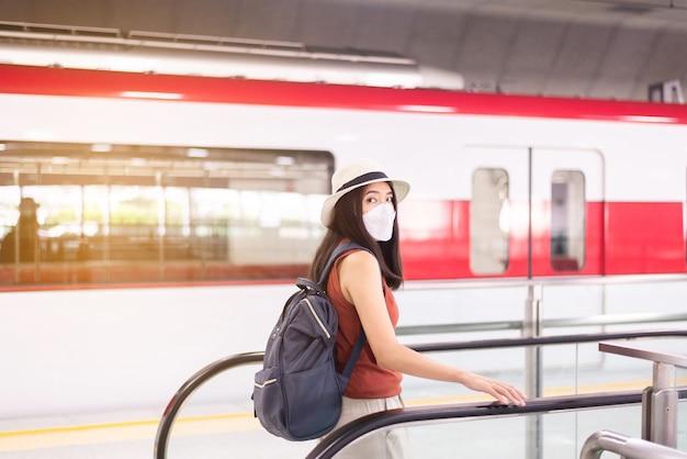 フェイスマスクを着用し、駅でエスカレーターを使用しているアジアの女性、公共交通機関の安全性、covid-19パンデミック中のニューノーマル