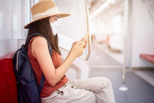 フェイスマスクを着用し、地下鉄の電車でスマートフォンを使用しているアジアの女性、公共交通機関の安全性、covid-19パンデミック中のニューノーマル