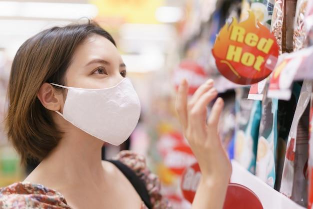 전염병 covid-19 동안 저녁 식사 시장에서 얼굴 마스크를 착용하는 아시아 여자.