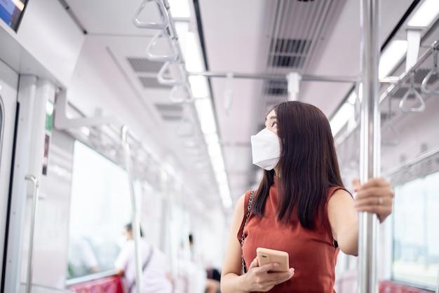 地下鉄の電車の中でサインとスケジュールを探しているフェイスマスクを身に着けているアジアの女性、公共交通機関の安全性、covid-19パンデミック中のニューノーマル