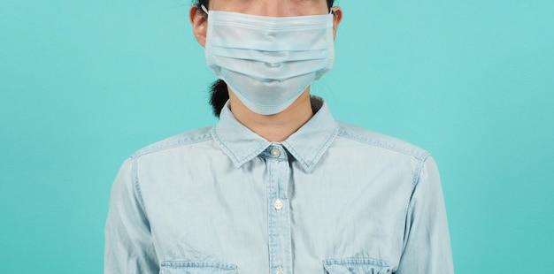 녹색 민트 또는 티파니 블루 배경에 얼굴 마스크를 쓴 아시아 여성. 스튜디오 초상화를 닫습니다.