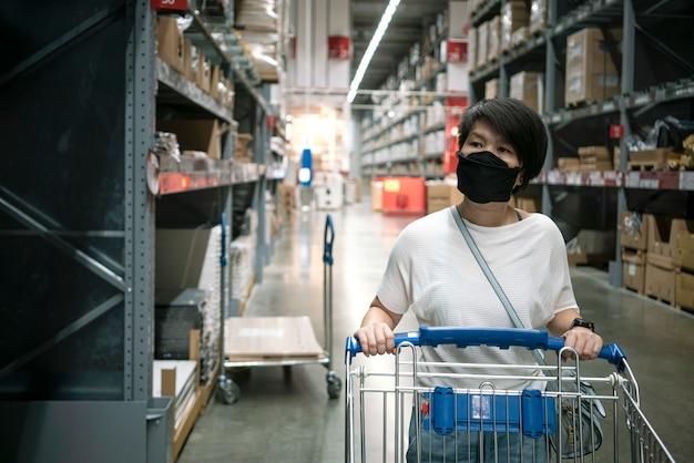 Азиатская женщина в маске для лица, выбирая товары в магазине