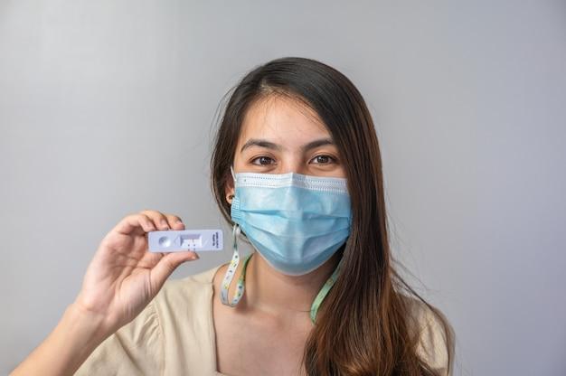 안면 마스크를 쓴 아시아 여성은 가정용 급속 항원 테스트 키트의 음성 결과를 보여줍니다. 코로나19, 코로나바이러스 감염 없음