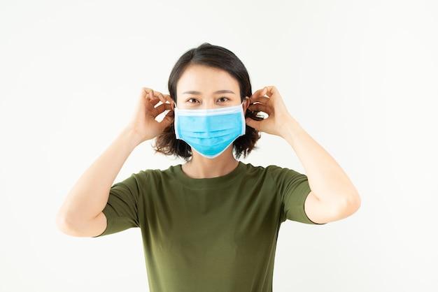 白い壁に大気汚染やウイルスの流行から保護するために顔のマスクを身に着けているアジアの女性