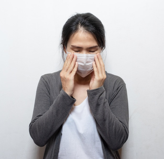 Asian woman wearing facial mask hands cover face and sneeze for protection from air pollution