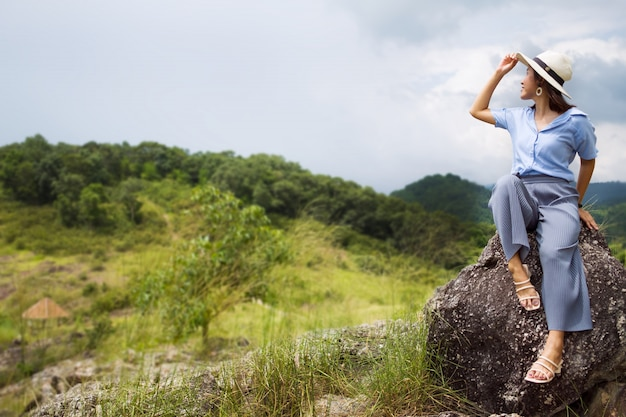Asian woman wearing a hat and casual dress was sitting on a large rock, her hand touched the hat