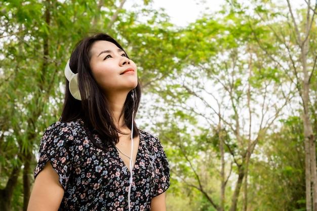 ドアの外で音楽を楽しんでいるヘッドフォンを身に着けているアジアの女性