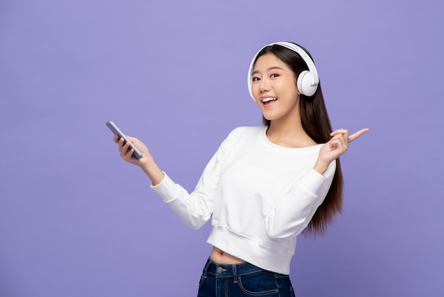 Asian woman wearing headphones listening to music from smartphone
