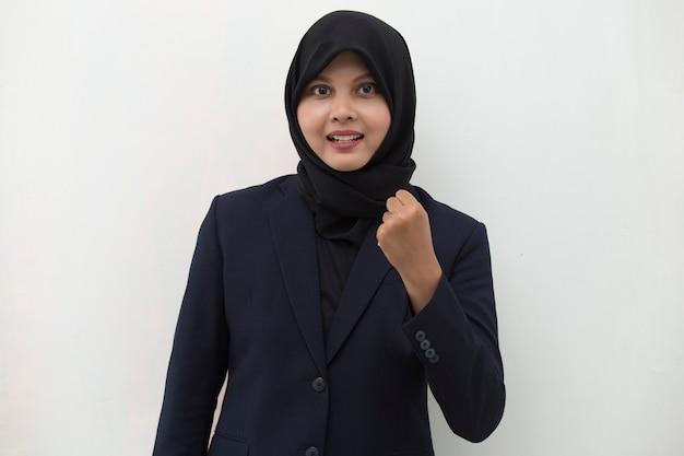 Азиатская женщина в хиджабе счастлива и взволнована, празднует победу, выражая большой успех, мощную энергию и положительные эмоции, радостно празднует новую работу