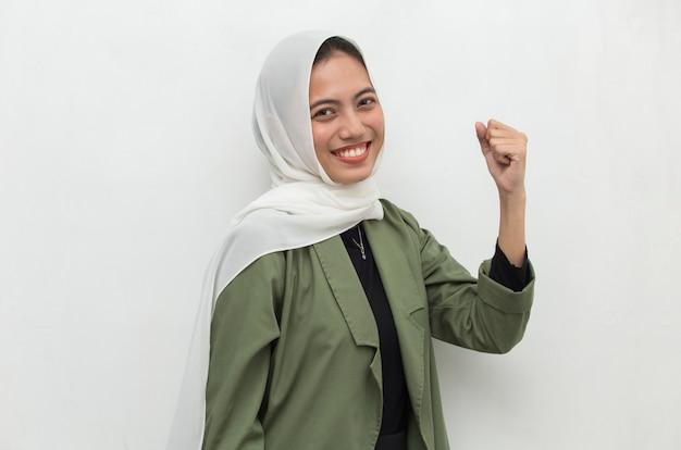 Азиатская женщина в хиджабе счастлива и взволнована, празднуя победу, выражая энергию большого успеха и положительные эмоции