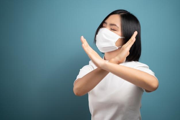 Азиатская женщина в гигиенической маске показывает скрещенными руками знак остановки и стоит изолированно над синим