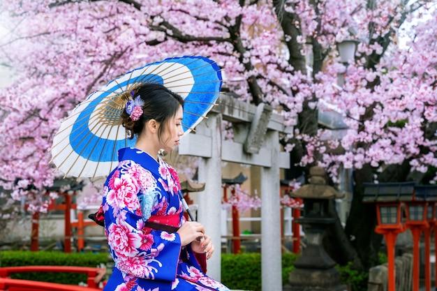 봄에 일본 전통 기모노와 벚꽃, 일본의 교토 사원을 입고 아시아 여자.