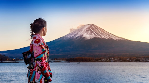 후지산에서 일본 전통 기모노를 입고 아시아 여자. 일본의 가와구치 코 호수에서 일몰.