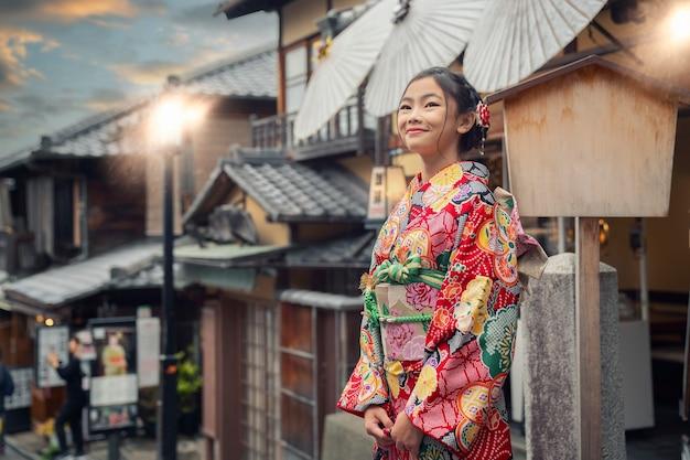Азиатская женщина в традиционном японском кимоно у пагоды ясака и на улице саннен дзака