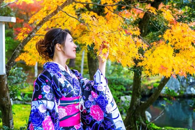 Donna asiatica che indossa il kimono tradizionale giapponese nella sosta di autunno. giappone