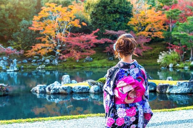 Азиатская женщина в традиционном японском кимоно в осеннем парке. япония