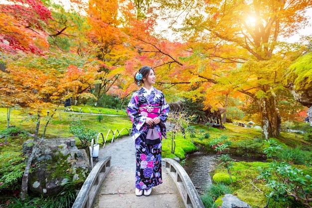 秋の公園で日本の伝統的な着物を着ているアジアの女性。日本の京都。