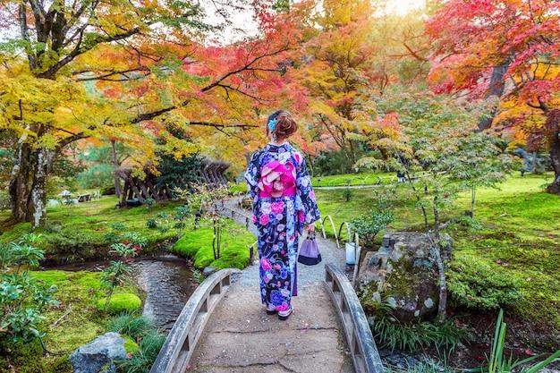 Азиатская женщина в традиционном японском кимоно в осеннем парке. киото в японии.