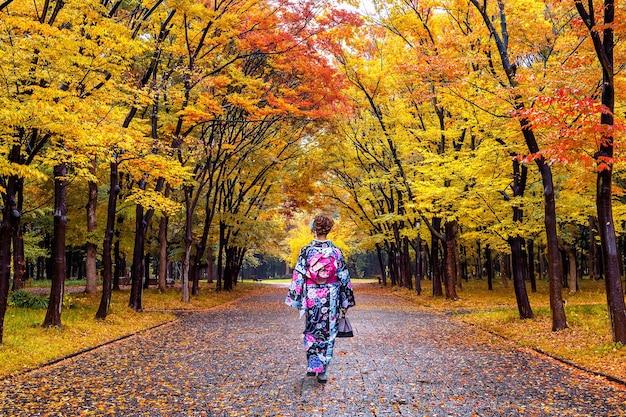 秋の公園で日本の伝統的な着物を着ているアジアの女性。