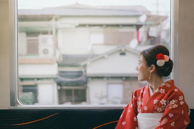 Asian woman wearing kimono traveling by the japan classic train sitting near the window