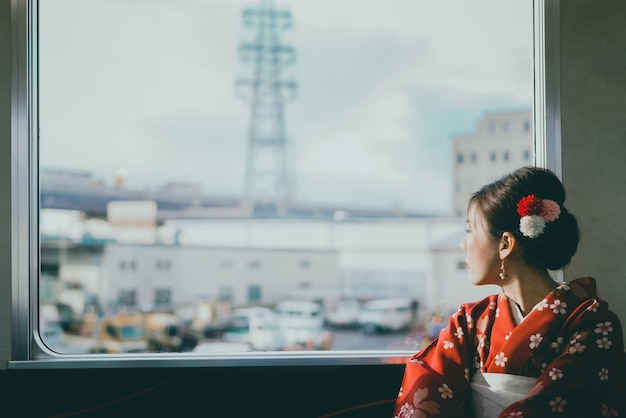 Asian woman wearing kimono traveling by the japan classic train sitting near the window