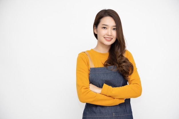 Asian woman wearing kitchen apron cooking and arms crossed