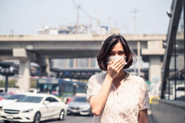 夕暮れpm 2.5の悪い空気汚染とコロナウイルスまたはcovid-19を防ぐためのマスクを身に着けているアジアの女性