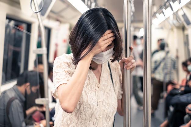 Азиатская женщина, носящая маску для предотвращения заката вечера 2.5 плохое загрязнение воздуха и коронавирус или ковид-19