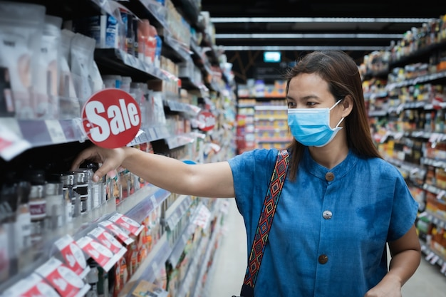 Asian woman wearing mask over her face while grocery shopping in supermarket for healthcare
