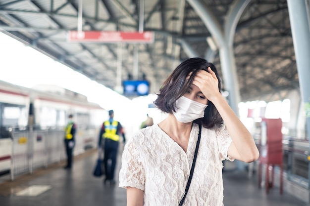 Asian woman wearing mask for prevent dusk pm 2.5 bad air pollution and coronavirus or covid-19 spreading over asia having headache sickness on sky train.