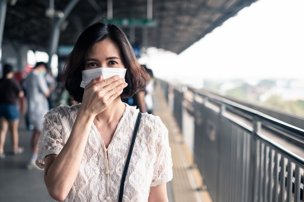 Asian woman wearing mask for prevent dusk pm 2.5 bad air pollution and coronavirus or covid-19 spreading over asia.