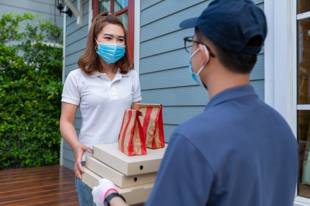 Asian woman wearing a mask receiving food package from delivery man at home concept service quarantine pandemic coronavirus virus [covid-19].