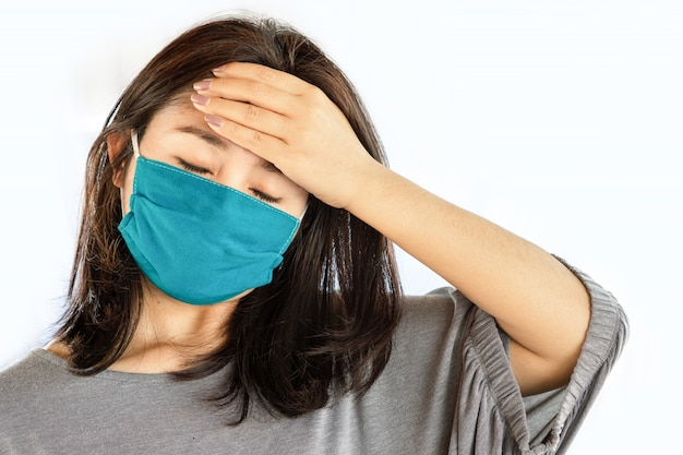 Asian woman wearing mask suffering from headache and flu