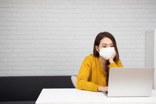 자가 격리 및 검역 중에 컴퓨터 노트북으로 깨어 있는 마스크를 쓴 아시아 여성