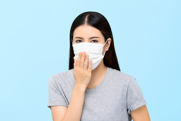 Asian woman wearing medical face mask coughing isolated on light blue background