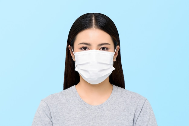 Asian woman wearing medical face mask isolated on light blue background