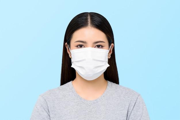 밝은 파란색 배경에 고립 된 의료 얼굴 마스크를 착용하는 아시아 여자