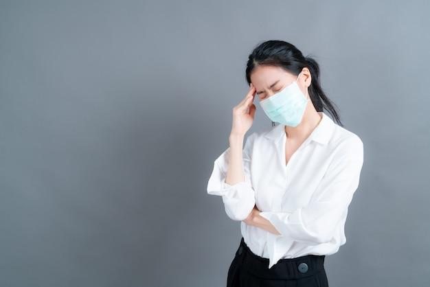 医療用フェイスマスクを着用しているアジアの女性は、フィルターダストpm2.5汚染防止、スモッグ防止、およびcovid-19を保護し、頭痛を持っています