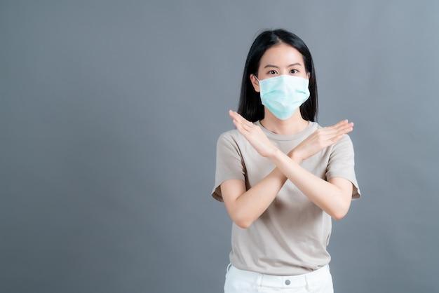 医療用フェイスマスクを着用しているアジアの女性は、灰色の壁にフィルターダストpm2.5汚染防止、スモッグ防止、およびcovid-19を保護します