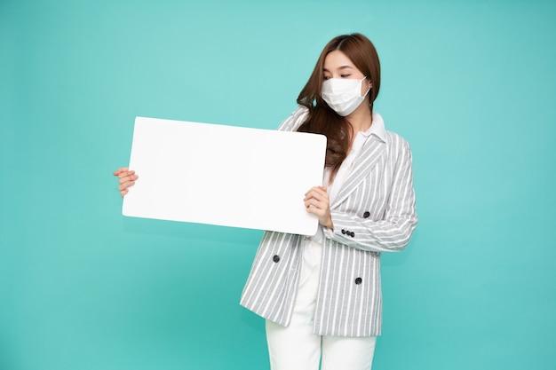 의료용 마스크를 쓰고 녹색 배경에 격리된 빈 흰색 광고판을 들고 있는 아시아 여성