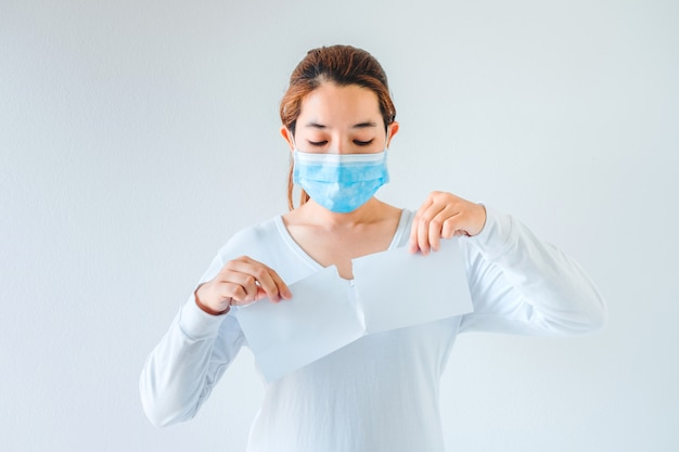 空白の白い紙を引き裂く医療マスクを身に着けているアジアの女性