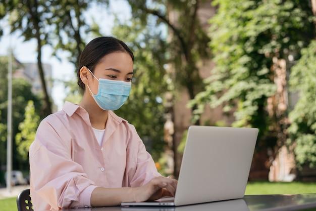 ラップトップコンピューターを使用して医療マスクを身に着けているアジアの女性