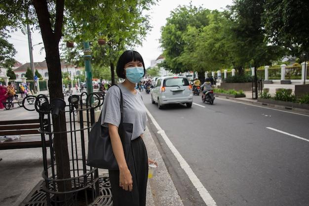 의료용 마스크를 쓴 아시아 여성이 대중 교통을 위해 밖에서 기다리고 있다