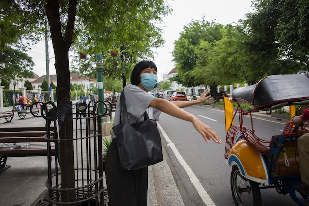 Asian woman wearing medical mask waiting outside for public transport