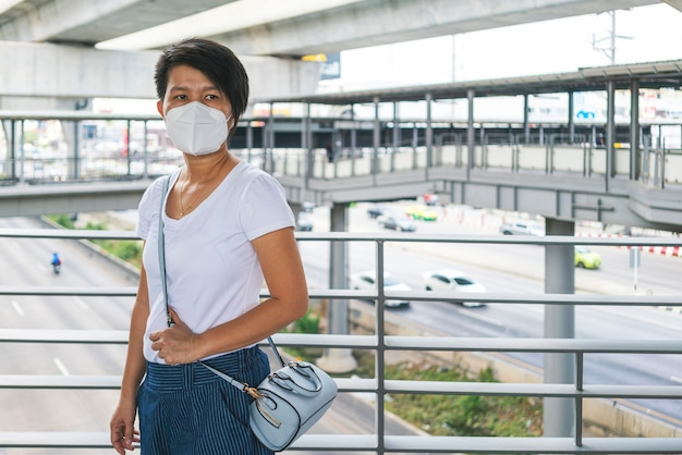 Asian woman wearing n95 face mask standing on sky walk during go to work